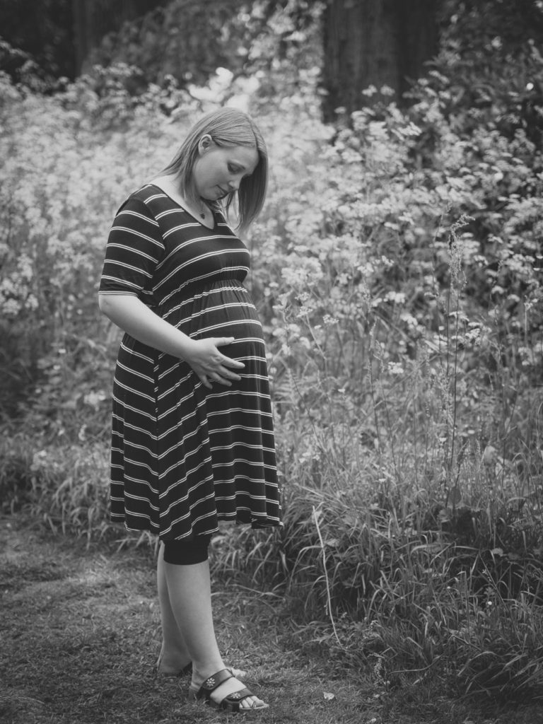 Portrait in black and white of Mel standing in field gently holding bump